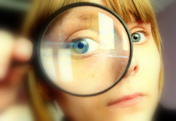 a person is holding a magnifying glass up to one eye